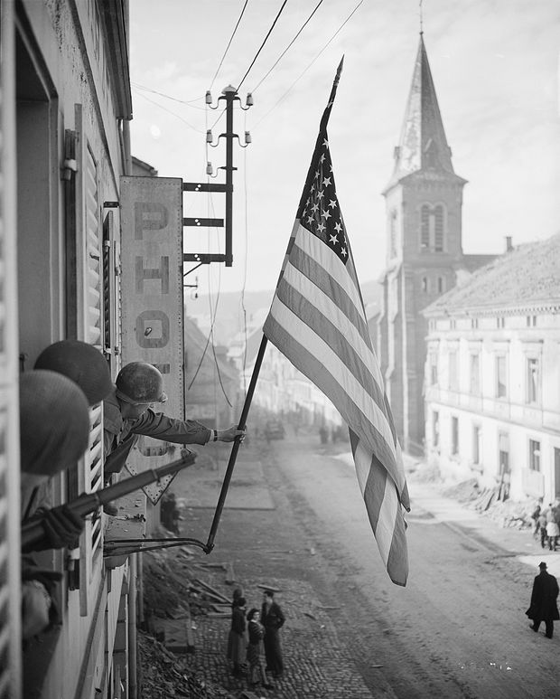 Captain Thomas H.'' Garahan Waving The American Flag After The Liberation Of The City Of Bitche (Bas-Rhin), One Of The Last Pockets Occupied By The Germans In Alsace. On March 17, 1945.