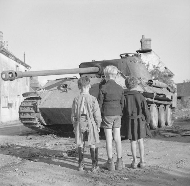 Three French Boys Look At A Knocked-Out German Panther Tank In The Falaise Pocket. Near Falaise, Lower Normandy, France. 25th August 1944.