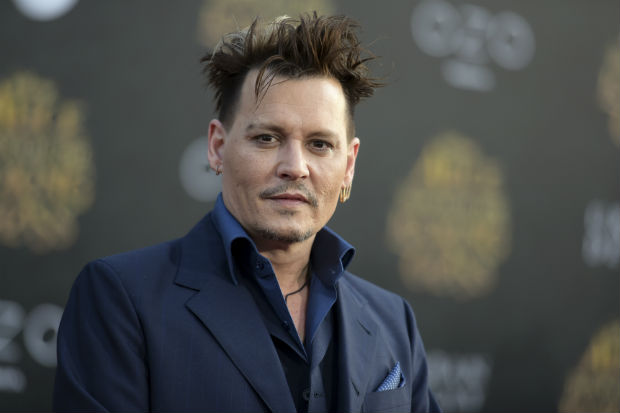 """FILE - In this May 23, 2016 file photo, Johnny Depp arrives at the premiere of """"Alice Through the Looking Glass"""" at the El Capitan Theatre, in Los Angeles. Depp is about to enter a world of magic. The actor is set to be part of """"Harry Potter"""" author J.K. Rowling's """"Fantastic Beasts and Where to Find Them"""" universe in a secretive role, according to a Warner Bros. representative Tuesday, Nov. 1, 2016. (Photo by Richard Shotwell/Invision/AP, File) ORG XMIT: CAET430"""
