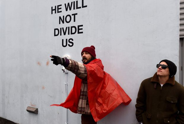"US actor Shia LaBeouf(L) during his ""He Will Not Divide Us"" livestream outside the Museum of the Moving Image in Astoria, in the Queens borough of New York January 24, 2017 as a protest against President Donald Trump. LaBeouf has installed a camera at the Museum of the Moving Image in New York that will run a continuous live stream for the duration of Trump's presidency. LaBeouf is inviting the public to participate in the project by saying the phrase, ""He will not divide us,"" into the camera. / AFP PHOTO / TIMOTHY A. CLARY ORG XMIT: TC050"