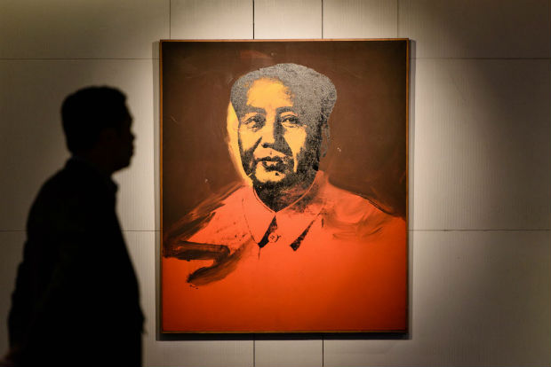(FILES) This file photo taken on March 17, 2017 shows a man walking past 'Mao' by US artist Andy Warhol, 1973, an acrylic and silkscreen ink on canvas, during a pre-auction preview by Sotheby's in Hong Kong. A classic Andy Warhol portrait of former Chinese leader Mao Zedong fetched US$12.7 million at auction in Hong Kong on April 2, Sotheby's said -- well short of the top estimate of more than $15 million. / AFP PHOTO / Anthony WALLACE / RESTRICTED TO EDITORIAL USE - MANDATORY MENTION OF THE ARTIST UPON PUBLICATION - TO ILLUSTRATE THE EVENT AS SPECIFIED IN THE CAPTION