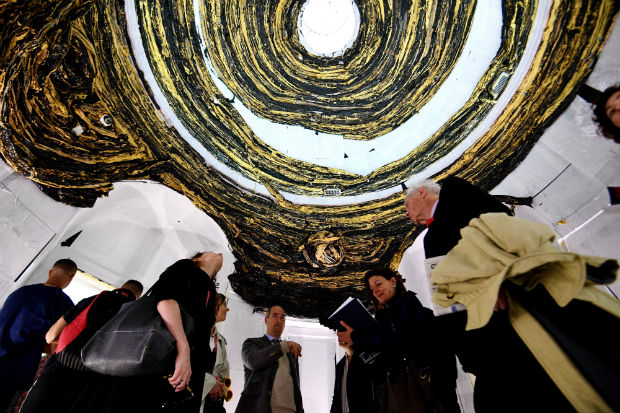 """Visitors admire the artwork """"Oracle"""" by US artist Mark Bradford on May 9, 2017, during a press preview of the 57th International Art Exhibition in Venice. The exhibition, titled """"Viva Arte Viva"""" is curated by Christine Macel and will be open to the public from May 13 to November 26, 2017 at the Giardini and Arsenale venues. / AFP PHOTO / Vincenzo PINTO / RESTRICTED TO EDITORIAL USE - MANDATORY MENTION OF THE ARTIST UPON PUBLICATION - TO ILLUSTRATE THE EVENT AS SPECIFIED IN THE CAPTION ORG XMIT: VIP015"""