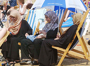 ORG XMIT: 411901_1.tif Three muslim women attempt to find some shade amongst sunbathers on the beach at Southend on Sea, England, Wednesday Aug, 6, 2003, as Britain continued to swelter in near record temperatures. (AP Photo/PA, Sean Dempsey ) ** UNITED KINGDOM OUT: MAGAZINES OUT: NO SALES: **