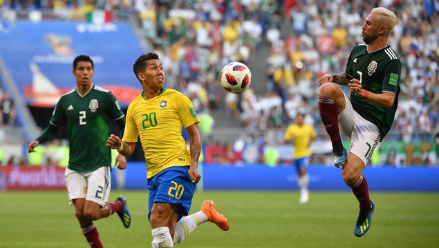 Roberto Firmino of Brazil vies with Miguel Layun of Mexico during the 2018 FIFA World Cup round of 16 match between Brazil and Mexico in Samara, Russia, July 2, 2018. Brazil won 2-0 and advanced to the quarter-final