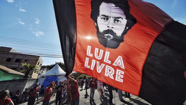 "In July 8, 2018 photo, a supporter of ex-President Luiz Inacio Lula da Silva holds a flag that reads in Portuguese: ""Free Lula,"" in front of the Federal Police Department where Da Silva is serving jail time in Curitiba, Brazil. A Brazilian appeals court judge has ordered Da Silva released from jail on, but another judge has asked the police to hold off on the order."