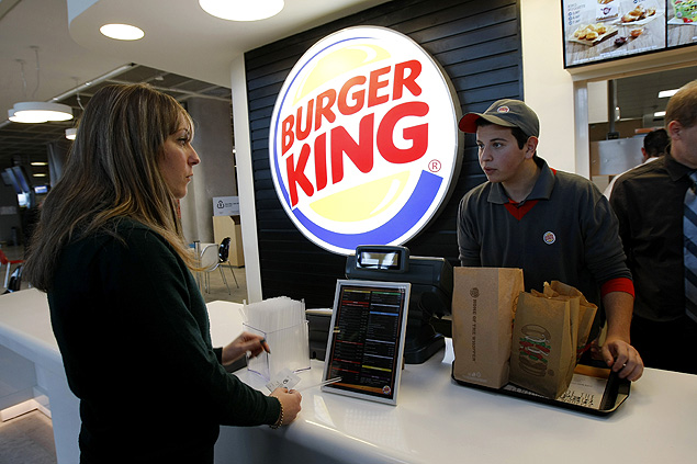 FILE - In a Saturday, Dec. 22, 2012 file photo, a customer purchases a meal at a Burger King restaurant in Marseille-Provence airport, in Marignane, France. Burger King is in talks to buy Tim Hortons in hopes of creating a new, publicly traded company with its headquarters in Canada. (AP Photo/Claude Paris, File) ORG XMIT: NY112