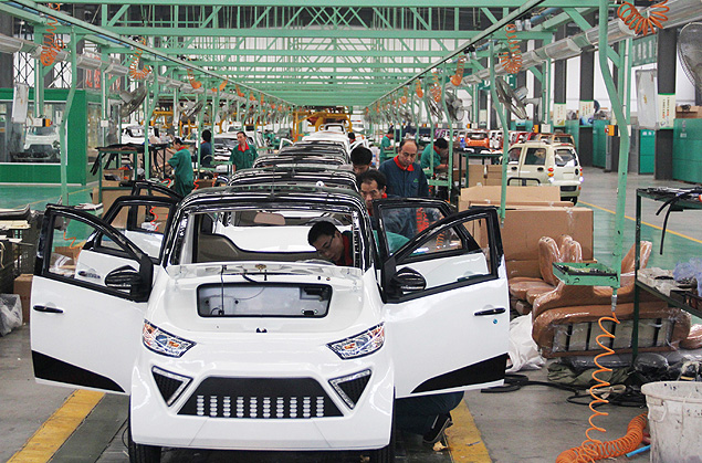 Workers assemble electric cars in a factory in Zouping, east China's Shandong province on September 16, 2014.China's outbound investment more than doubled in August to 12.62 billion USD, data showed, far outstripping foreign direct investment (FDI) into the country, which fell to a four-year low. CHINA OUT AFP PHOTO ORG XMIT: WH5767