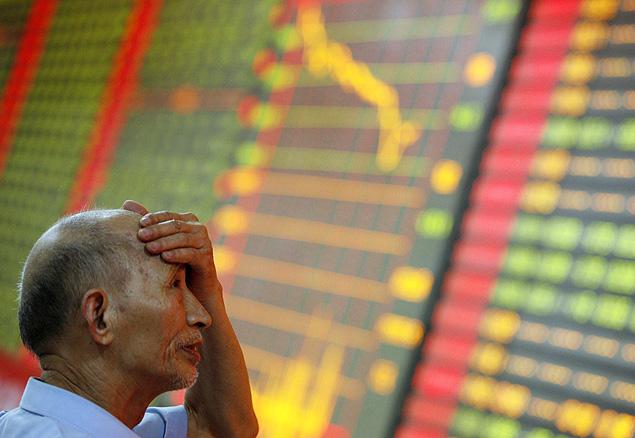 Homem observa painel com dados sobre ações na Bolsa de Xangai, em Huaibei (China)