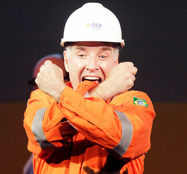 Brazilian billionaire Eike Batista (L), CEO of EBX Group, gestures to the audience during a ceremony in celebration of the start of oil production of OGX, his oil and gas company, at the Superport Industrial Complex of Acu in Sao Joao da Barra in Rio de Janeiro in this April 26, 2012 file photo. As Batista's EBX industrial empire crumbles, it increasingly resembles his most visible accomplishment, the Port of Acu. In other words, a pile of sand in the middle of a swamp. To build the $2 billion iron ore and oil terminal, shipyard and industrial park 300 kilometers (190 miles) north of Rio de Janeiro, the world's largest dredging ship cut through the beach and dug 13 kilometers (8 miles) of docks out of dune and marsh. To keep tenants dry, the sandy waste is being piled as much as 15 meters over the surrounding flood plain. Picture taken April 26, 2012. To match Analysis BRAZIL-BATISTA/ REUTERS/Ricardo Moraes/Files (BRAZIL - Tags: ENERGY BUSINESS) ORG XMIT: RJO89 ***FOTO EM ARTE E NÃO INDEXADA***