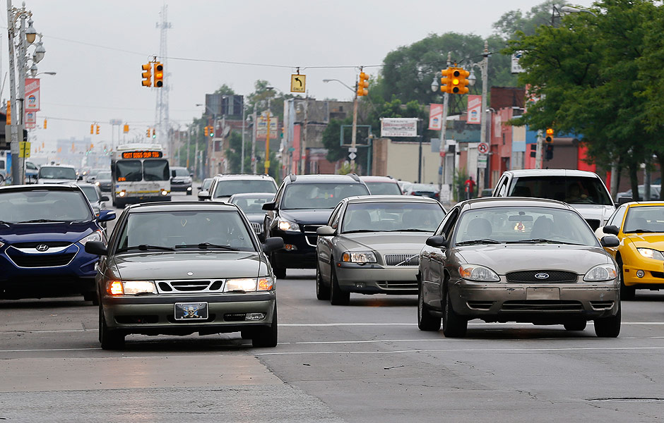 In this Thursday, July 9, 2015 photo, motorists drive on Grand River Boulevard in Detroit. It's called driving dirty and city officials estimate that one out of every two motorists living in Detroit is taking to the road without any type of auto insurance coverage. Data from CarInsurance.com shows the top 25 zip codes in the United States where drivers pay the most for car insurance are in Detroit, with some policies topping $5,000 annually. (AP Photo/Paul Sancya) ORG XMIT: MIPS101