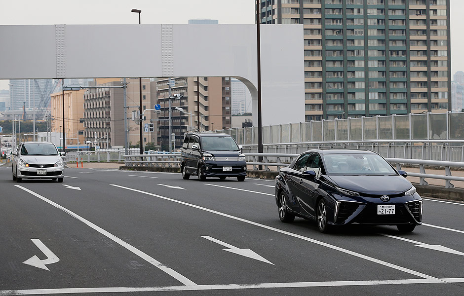 In this photo taken Monday, Nov. 17, 2014, a Toyota Motor Corp.'s new fuel cell vehicle Mirai, right, drives by on the road near its showroom in Tokyo. There will only be a few hundred, and they won't be cheap, but Toyota is about to take its first small step into the unproven market for emissions-free, hydrogen-powered vehicles. The world's largest automaker announced Tuesday, Nov. 18 that it will begin selling fuel cell cars in Japan on Dec. 15 and in the U.S. and Europe in mid-2015. The sporty-looking, four-door Toyota Mirai will retail for 6.7 million yen ($57,600) before taxes. (AP Photo/Shizuo Kambayashi) ORG XMIT: XKAN209