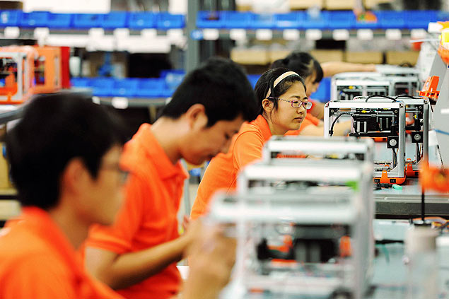 Workers assemble 3D printers in a factory in Qingdao in eastern China's Shandong province, Tuesday Sept. 1, 2015. Chinese manufacturing showed further signs of weakness in August, adding to evidence of an inexorable slowdown in the world's No. 2 economy despite recent government efforts to support growth. (Chinatopix Via AP) CHINA OUT ORG XMIT: XMAS803 digitalização