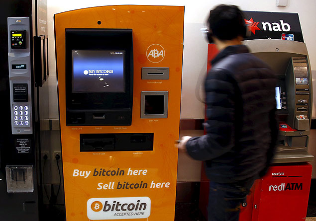 A customer of an Australian bank walks away after withdrawing money from an Automatic Teller Machine (ATM) located next to a Bitcoin ATM at a shopping mall in central Sydney, Australia, October 1, 2015. Australian businesses are turning their backs on bitcoin, as signs grow that the cryptocurrency's mainstream appeal is fading. Concerns about bitcoin's potential crime links mean many businesses have stopped accepting it, a trend accelerated by Australian banks' move last month to close the accounts of 13 of the country's 17 bitcoin exchanges.. Picture taken October 1, 2015. REUTERS/David Gray ORG XMIT: DBG305