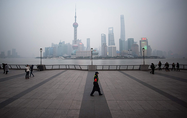TOPSHOT - A security guard walks at the bund near the Huangpu river across the Pudong New Financial district, in Shanghai on January 18, 2016. China recorded its lowest growth in a quarter of a century in 2015, an AFP survey has forecast, projecting a further slowdown in the world's second-largest economy this year. AFP PHOTO / JOHANNES EISELE / AFP / JOHANNES EISELE ORG XMIT: EIS03
