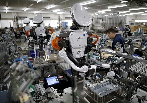 Humanoid robots work side by side with employees in the assembly line at a factory of Glory Ltd., a manufacturer of automatic change dispensers, in Kazo, north of Tokyo, Japan, July 1, 2015. REUTERS/Issei Kato/File Photo GLOBAL BUSINESS WEEK AHEAD PACKAGE Ð SEARCH ÒBUSINESS WEEK AHEAD JUNE 13Ó FOR ALL IMAGES ORG XMIT: BWA403