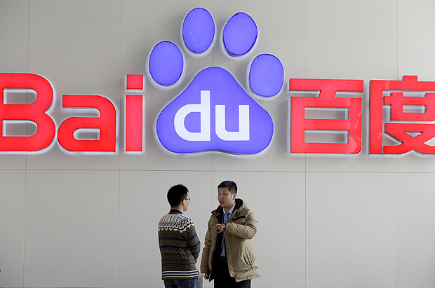 People talk in front of Baidu's company logo at its headquarters in Beijing, China, in this January 16, 2014 file picture. China's dominant Internet search engine Baidu Inc on April 30, 2015 posted its slowest revenue growth rate in almost seven years in the first quarter of 2015, as customers spent less money on its core online marketing business. REUTERS/Jason Lee/Files ORG XMIT: PEK02