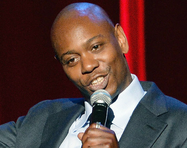 """""""I know my show is protected, and it empowers me to be more honest and open with the audience,"""" the comedian Dave Chappelle said of using Yondr pouches to lock fans' cellphones during performances. Credit Mike Coppola/Getty Images"""