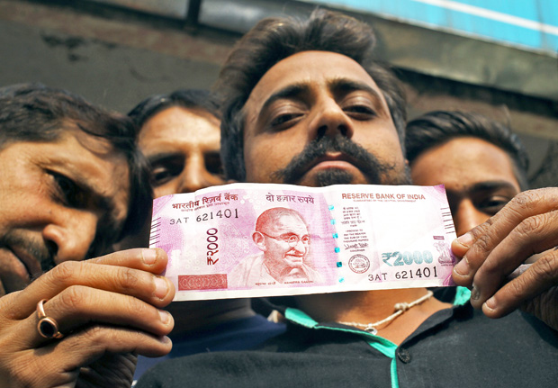 A man displays a new 2000 Indian rupee banknote after withdrawing from a bank in Jammu, November 11, 2016. REUTERS/Mukesh Gupta ORG XMIT: DEL11