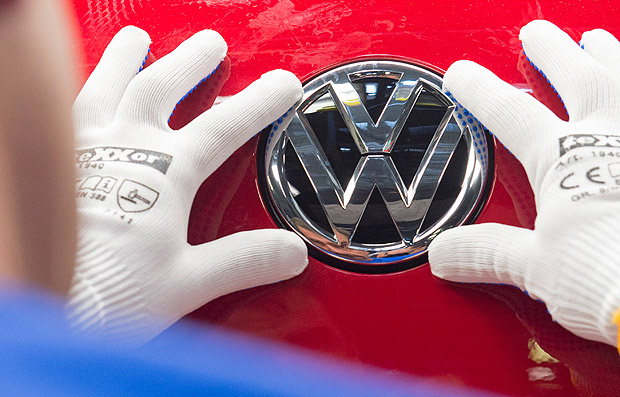 FILE - In this Sept. 6, 2016 file photo a worker checks the Volkswagen sign on a Golf car during the so called 'Open Door Day' to celebrate the 25th anniversary of the German manufacturer Volkswagen Sachsen in Zwickau, eastern Germany. Volkswagen will announce its future strategy which might include job cuts in a press conference on Friday, Nov. 18, 2016. (AP Photo/Jens Meyer, file) ORG XMIT: FOS102