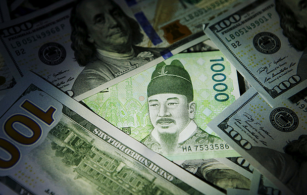 South Korean 10,000 won note is seen on U.S. 100 dollar notes in this picture illustration taken in Seoul, South Korea, December 15, 2015. REUTERS/Kim Hong-Ji/File Photo ORG XMIT: RPA420