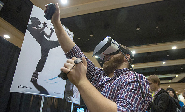 A man experiences a Taclim virtual reality system wearing VR shoes and gloves with built-in tactile devices to provide haptic feedback during the 2017 Consumer Electronics Show (CES) in Las Vegas, Nevada on January 3, 2017. / AFP PHOTO / DAVID MCNEW