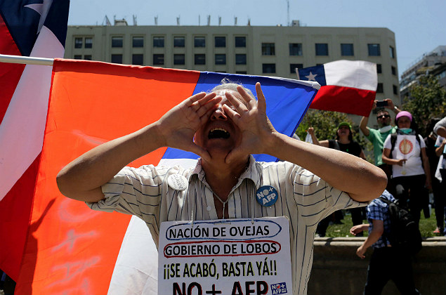 "A demonstrator wearing a banner that reads ""Nation of sheeps, Government of wolfs. No more AFP"" (Pension Fund Administrators)"" shouts slogans in front of the government house during a protest a day after Congress approved a relatively small 2017 wage hike for workers of the public sector, in Santiago, Chile, November 17, 2016. REUTERS/Pablo Sanhueza EDITORIAL USE ONLY. NO ARCHIVES. NO RESALES. ORG XMIT: IA104"