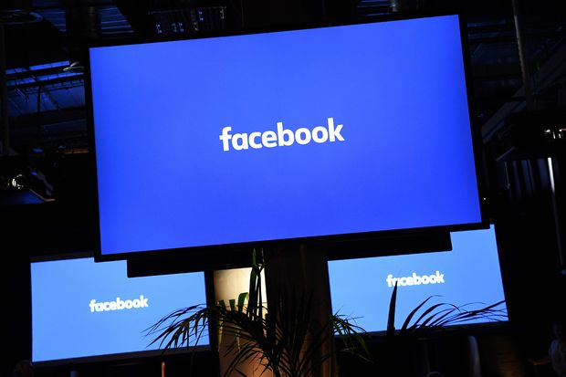 A Facebook logo is pictured on a screen, in central London