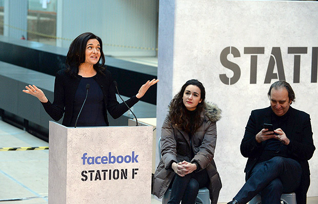 """Facebook Chief Operating Officer Sheryl Sandberg (L) gives a press conference next to French businessman and founder of start-up incubator """"Station F"""" Xavier Niel (R) and head of Station F Roxanne Varza at Station F headquarters in Paris on January 17, 2017. / AFP PHOTO / ERIC PIERMONT ORG XMIT: EP6519"""