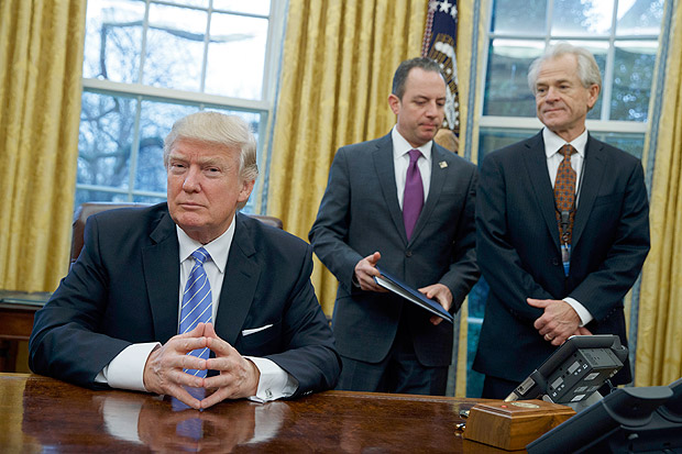 National Trade Council adviser Peter Navarro, right, and White House Chief of Staff Reince Priebus, center, await President Donald Trump's signing three executive orders, Monday, Jan. 23, 2017, in the Oval Office of the White House in Washington. (AP Photo/Evan Vucci) ORG XMIT: DCEV113