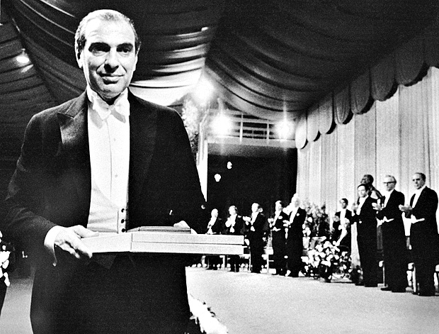Kenneth J. Arrow of Harvard University carries his Nobel prize for economic science after receiving it in solemn ceremonies at Stockholm, Sweden, Dec. 10, 1972. On stage in the background are other Nobel laureates. Medals, diplomas and checks were presented to a record 11 prize winners - eight Americans, two Britons and a German. (AP Photo) ORG XMIT: APHS81804 ***DIREITOS RESERVADOS. N�O PUBLICAR SEM AUTORIZA��O DO DETENTOR DOS DIREITOS AUTORAIS E DE IMAGEM***