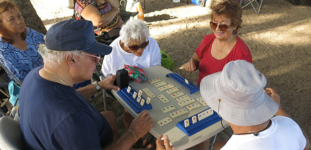 A group of retired friends play a table top game at the beach in San Juan, Puerto Rico, Thursday, Feb. 9, 2017. The group meets at the beach meet twice a week as they enjoy their retirement. The U.S. territory's public pension system faces a $40 million deficit and is expected to collapse within a year, threatening to plunge into poverty a significant portion of a booming elderly population already struggling with higher taxes and medical bills amid an economic crisis. (AP Photo/Danica Coto) ORG XMIT: RPTDC306