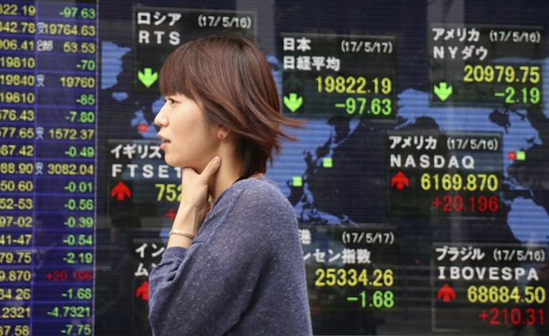 A woman walks past an electronic stock indicator of a securities firm in Tokyo, Wednesday, May 17, 2017. Asian stock markets were mostly lower on Wednesday as a rise in political uncertainties dented risk sentiment with investors keeping their eyes on developments in the White House.
