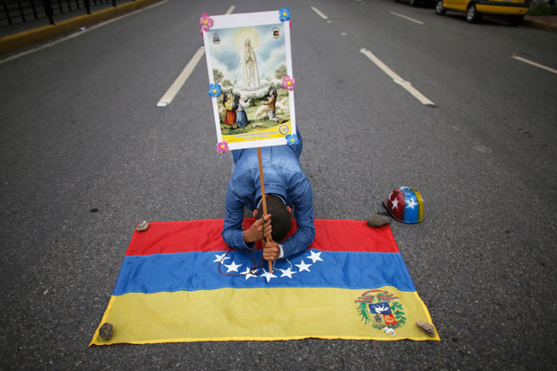 An anti-government demonstrator prays while kneeling on a Venezuelan flag as he holds a poster of the Virgin of Fatima, in Caracas, Venezuela, Saturday, June 17, 2017. Hundreds of thousands of demonstrators have taken to the streets demanding new elections as the nation battles triple-digit inflation, crippling food and medical shortages and rising crime.(AP Photo/Ariana Cubillos) ORG XMIT: XAC101