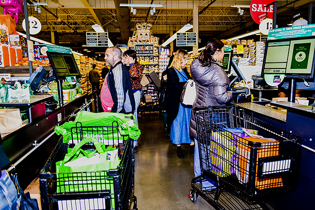 FILE - Customers check out at a Whole Foods in New York, Oct. 30, 2015. By purchasing the upscale grocery chain, Jeff Bezos, Amazon's chief, has a chance to tinker with how people buy groceries - and map the future of the physical store. (Dolly Faibyshev/The New York Times)