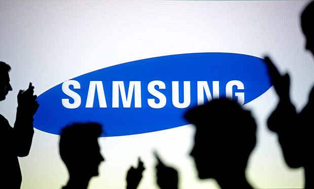 FILE PHOTO - People are silhouetted as they pose with mobile devices in front of a screen projected with a Samsung logo, in this picture illustration October 29, 2014. REUTERS/Dado Ruvic/Illustration/File Photo TPX IMAGES OF THE DAY ORG XMIT: SIN201