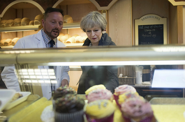 Britain's Prime Minister Theresa May looks at the cake counter as she makes a visit to a bakery in Fleetwood, northwest England while on the General Election campaign trail Tuesday June 6, 2017. Britain will hold a parliamentary election on Thursday. (Stefan Rousseau/PA via AP) ORG XMIT: LON801