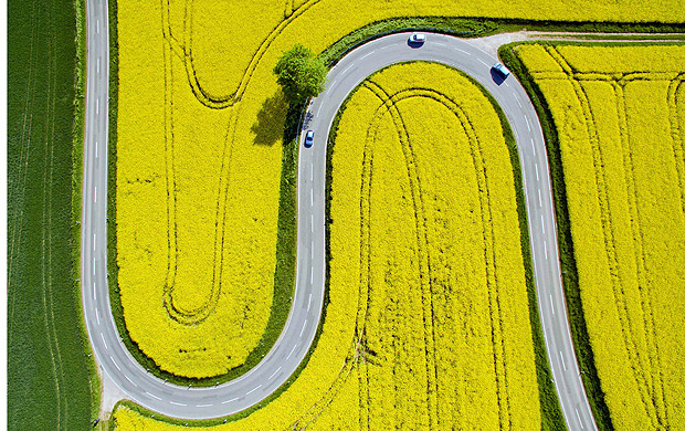 TOPSHOT - Aerial view taken on May 12, 2016 shows cars driving on the winding L401 country road past rapeseed fields near Nienstedt close to Bad Muender am Deister, central Germany. / AFP PHOTO / dpa / Julian Stratenschulte / Germany OUT ORG XMIT: jst120