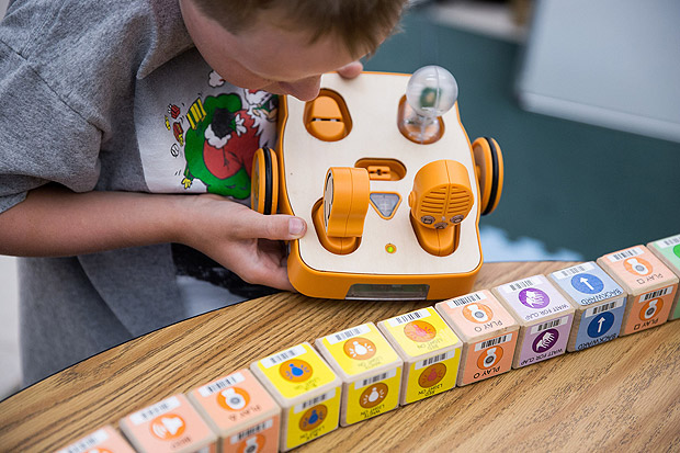 Henry Sayre, 8, scans a sequence of wooden blocks with a Kibo robot at DevTech summer camp at Tufts University in Medford, Mass. It introduces children to skills like building prototypes, debugging and coping with failure.CreditKayana Szymczak for The New York Times