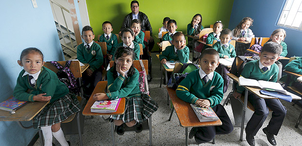 "Teacher Father Juan Humberto Cruz poses for pictures with 4th grade students at Semillas de Esperanza (Seeds of Hope) school in Soacha, near Bogota, Colombia, June 11, 2015. Nearly three years after Taliban gunmen shot Pakistani schoolgirl Malala Yousafzai, the teenage activist last week urged world leaders gathered in New York to help millions more children go to school. World Teachers' Day falls on 5 October, a Unesco initiative highlighting the work of educators struggling to teach children amid intimidation in Pakistan, conflict in Syria or poverty in Vietnam. Even so, there have been some improvements: the number of children not attending primary school has plummeted to an estimated 57 million worldwide in 2015, the U.N. says, down from 100 million 15 years ago. Reuters photographers have documented learning around the world, from well-resourced schools to pupils crammed into corridors in the Philippines, on boats in Brazil or in crowded classrooms in Burundi. REUTERS/John Vizcaino PICTURE 9 OF 47 FOR WIDER IMAGE STORY ""SCHOOLS AROUND THE WORLD""SEARCH ""EDUCATORS SCHOOLS"" FOR ALL IMAGES ORG XMIT: PXP09"