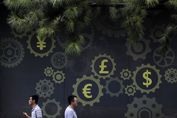Pedestrians pass by a billboard with foreign currency signs on display outside a bank in Beijing, Tuesday, July 18, 2017. China's economic growth held steady in the latest quarter, boosted by unexpectedly strong trade and consumer spending, despite fears tighter lending controls aimed at cooling a surge in debt are weighing on commercial activity. (AP Photo/Andy Wong) ORG XMIT: XAW104