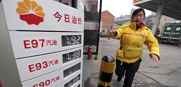 ORG XMIT: PEK04 An employee gestures to stop a photographer from taking pictures near a board showing recently increased fuel prices at a gas station in Hefei, Anhui province April 7, 2011. China will increase retail gasoline and diesel prices by 5-5.5 percent to new record highs from Thursday, the government said, easing the burden of state refiners who face international oil prices at 2.5-year highs. REUTERS/Stringer (CHINA - Tags: BUSINESS ENERGY)