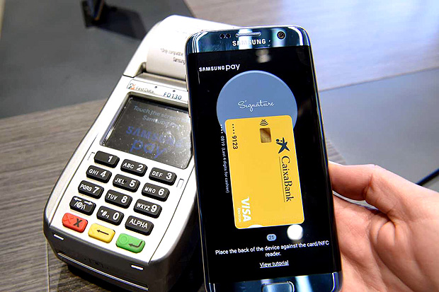 """A person shows the """"Samsung Pay"""" system on the first day of the Mobile World Congress in Barcelonaon on February 27, 2017 in Barcelona. Phone makers will seek to seduce new buyers with artificial intelligence functions and other innovations at the world's biggest mobile fair starting today in Spain. / AFP PHOTO / LLUIS GENE ORG XMIT: LG5071"""