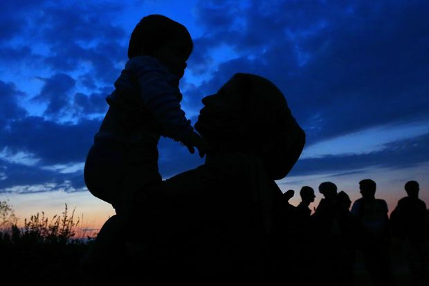 TOPSHOTS A woman holds a child as migrants wait to board a bus heading to the refugee camp in Opatovac, near the Croatian-Serbian border on September 23, 2015. More than 300,000 migrants have arrived by sea in Greece since January, the majority of whom continue their journey through Macedonia and Serbia on their way to EU countries Hungary and Croatia. AFP PHOTO / STRINGER ORG XMIT: AND004