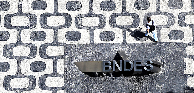 A man walks past the logo of Brazilian Development Bank (BNDES) at the entrance of its headquarters in Rio de Janeiro