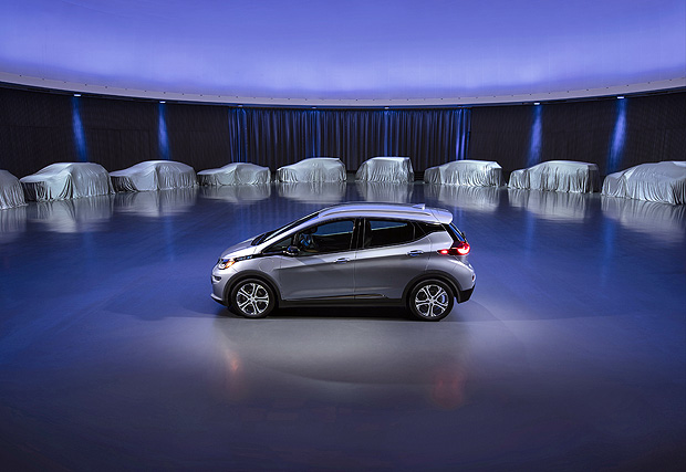 This photo provided by General Motors Co. shows a Chevrolet Bolt, surrounded by nine electric and fuel cell vehicles covered by tarps. On Monday, Oct. 2, 2017, GM announced the company will produce two new electric vehicles on the Bolt underpinnings in the next 18 months and 20 electric and hydrogen fuel cell vehicles by 2023. (Courtesy of General Motors Co. via AP) ORG XMIT: NYBZ112