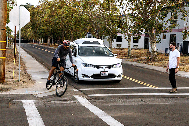 This Sunday, Oct. 29, 2017, photo provided by Waymo shows a Chrysler Pacifica minivan equipped with Waymo's self-driving car technology, being tested with the company's employees as a biker and a pedestrian at Waymo's facility in Atwater, Calif. Waymo, hatched from a Google project started eight years ago, showed off its progress Monday during a rare peek at a closely guarded testing facility located 120 miles southeast of San Francisco where its robots complete their equivalent to driver's education. (Julia Wang/Waymo via AP) ORG XMIT: NYHK201