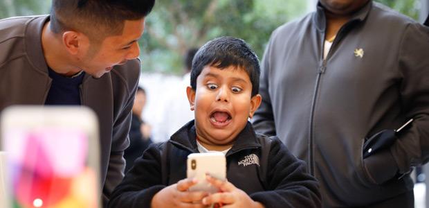 A boy makes faces while testing out the Animoji feature on an iPhone X at the Apple Store Union Square on November 3, 2017, in San Francisco, California. Apple's flagship iPhone X hits stores around the world as the company predicts bumper sales despite the handset's eye-watering price tag, and celebrates a surge in profits. / AFP PHOTO / Elijah Nouvelage