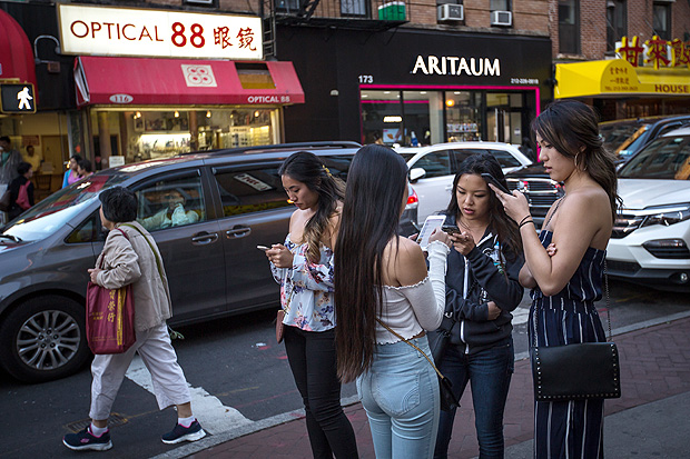 FILE -- People on their phones in Manhattan's Chinatown neighborhood, Sept. 9, 2017. Facebook announced sweeping changes to its News Feed on Jan. 11, 2018, saying that it would prioritize what their friends and family share and comment on while de-emphasizing content from publishers and brands. (Ali Asaei/The New York Times)