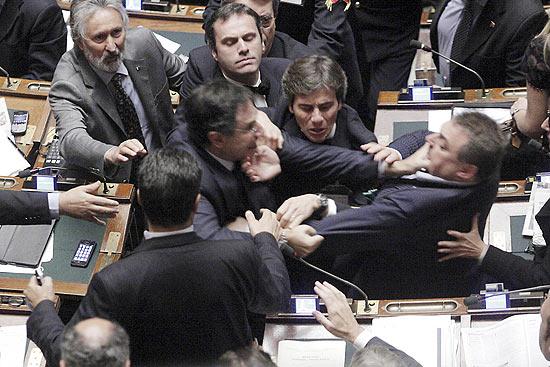 Claudio Barbato (esq.), do partido opositor FLI, segura o pescoço de Fabio Ranieri (dir.), da Liga Norte