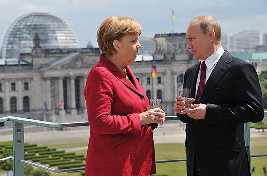 ORG XMIT: MOW020 With the Reichstag building in the background Russia's President Vladimir Putin speaks with German Chancellor Angela Merkel on the roof of the Chancellery in Berlin, on June 1, 2012. The main topic of Putin's meeting with Angela Merkel was the unrest in Syria, as Western powers attempt to persuade the Kremlin to drop its support for the regime of Bashir al-Assad. AFP PHOTO/ RIA-NOVOSTI/ POOL / ALEXEI NIKOLSKY